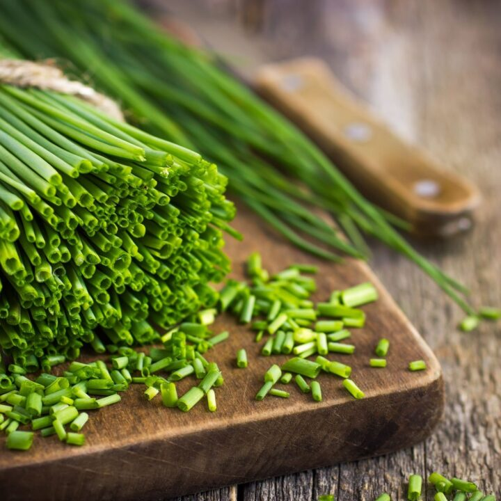 How to Grow Chives - Chives being Chopped on a Rustic Cutting Board