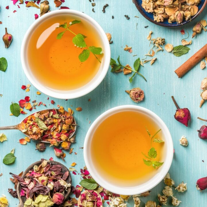 How to Grow a Tea Garden - Tea Garden Plants - Two mugs of tea surrounded by dried herbs