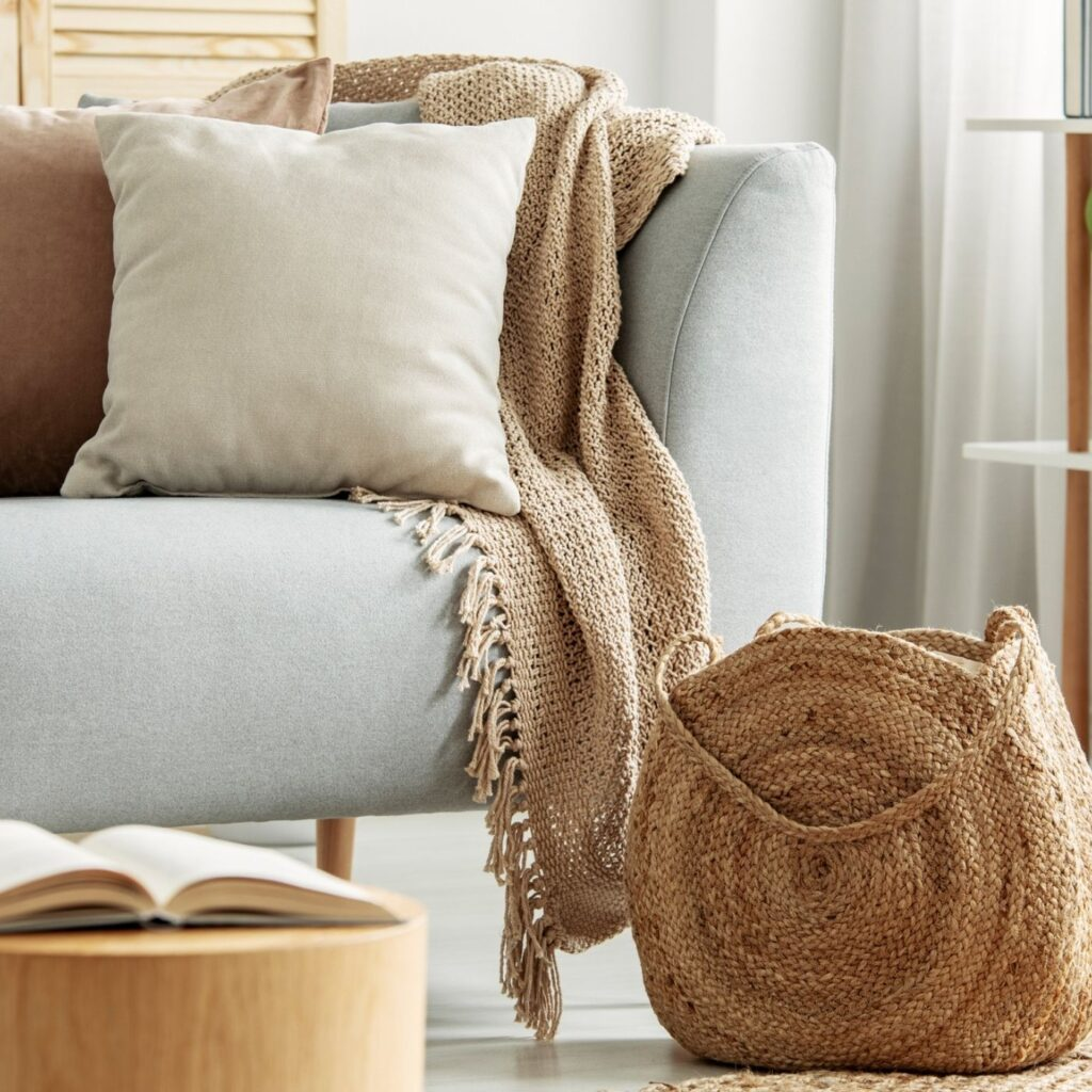 How to Keep a Tidy Home - Partial view of a gray couch with tan pillows, blanket and a bag
