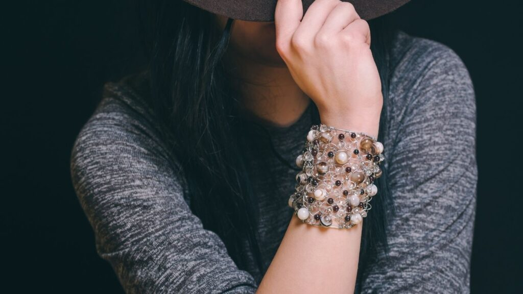 Hygge Clothing Ideas - Woman with comfortable top, bracelet and hat - her face is hidden.
