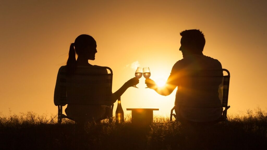 Hygge Cozy Dates - a couple toasting wine at sunset outdoors.