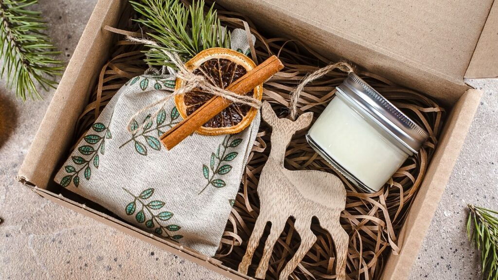 Hygge gift ideas - cardboard box with potpourri in a fabric bag with a dried orange and cinnamon stick, wooden deer ornament, and candle.