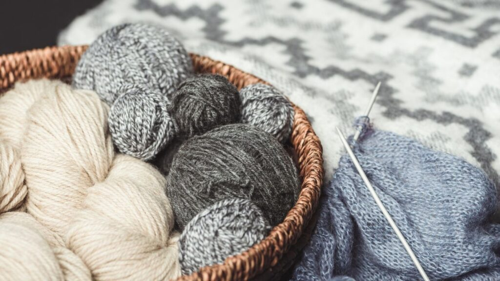 31 Hygge Hobbies to Try - wicker basket with balls of yarn and knitting project next to it.