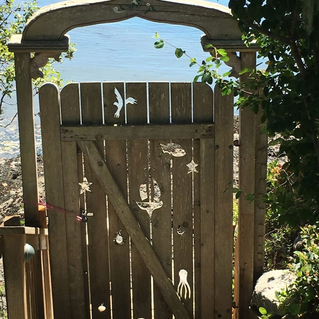 Nautical Garden Gate with cut-outs of sea creatures from the wooden gate.  Fun Ideas for Garden Decor