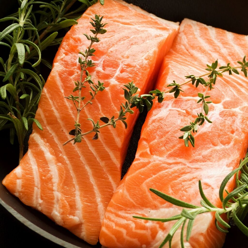 Raw salmon and fresh herbs in a cast iron skillet