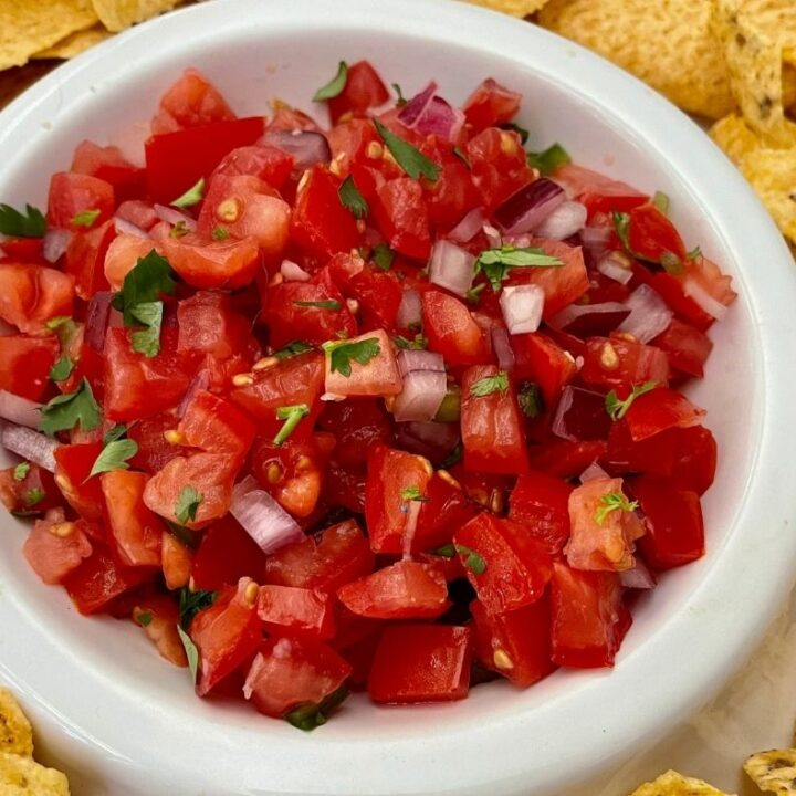Recipe for Salsa Fresca in a white bowl surrounded by tortilla chips