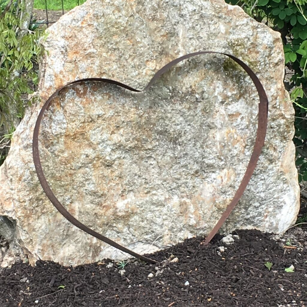 Rustic Garden Art - Love at Home - Metal Heart in front of a white rock