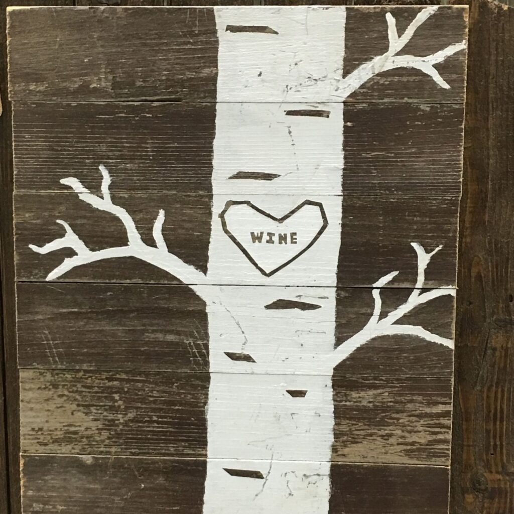 """Rustic garden sign with the base of a tree with a heart and the word """"wine"""" inside the heart."""