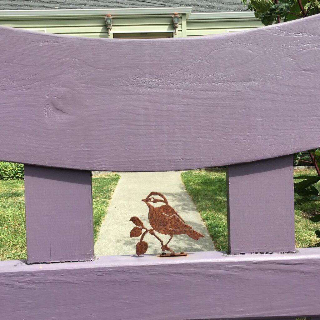 Fun Ideas for Garden Decor - Little rusty metal bird in the center of a wooden garden gate