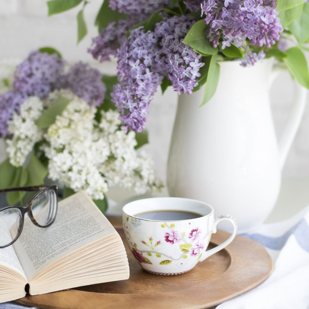 Wooden tray with mug of coffee, book, glasses, and pitcher with lilacs.
