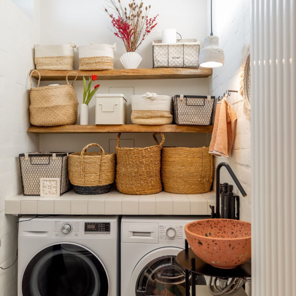 Tidy Home with the right equipment - Laundry room with washer and dryer and baskets above on shelves