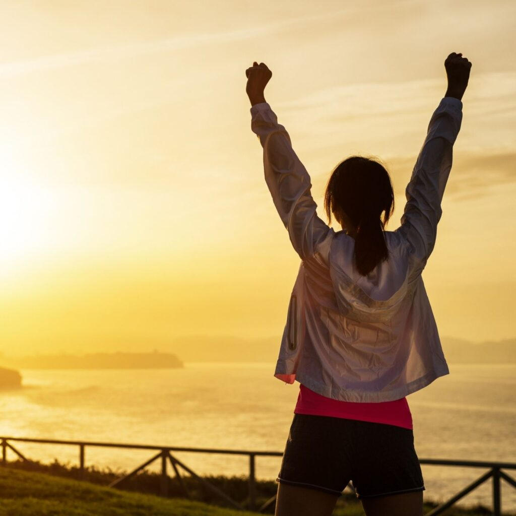 31 Small Goals Easily Achieved in 2021 - Woman at sunrise with her fists up in the air