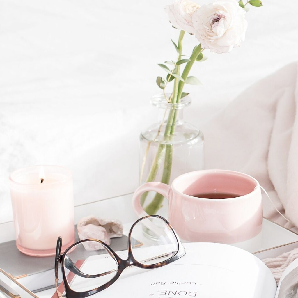 55 Simple Pleasures in Life - Bed side table with coffee mug, vase with rose, candle, and glasses.