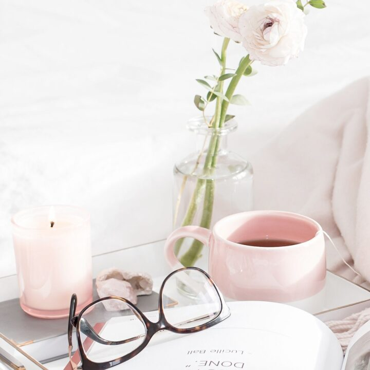 55 Simple Pleasures in Life - side table with candle, vase with rose, mug, glasses
