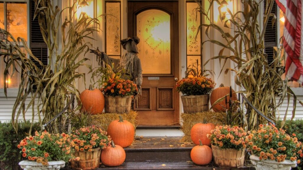 Halloween front porch with cornstalks, pumpkins, hay bales, mums, and a scarecrow