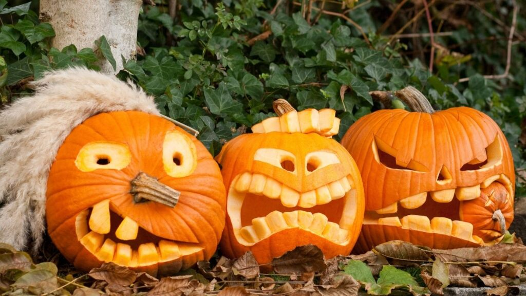 """A trio of Halloween carved pumpkins.  One of them has """"hair"""" from a dried feather plant."""
