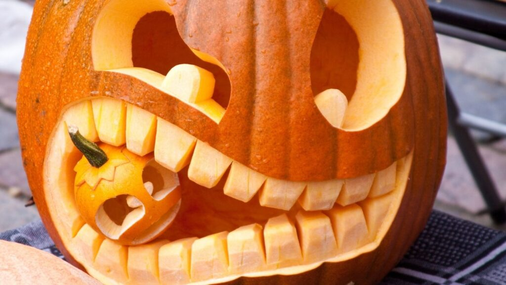 Carved Halloween pumpkin with it's mouth eating another mini pumpkin