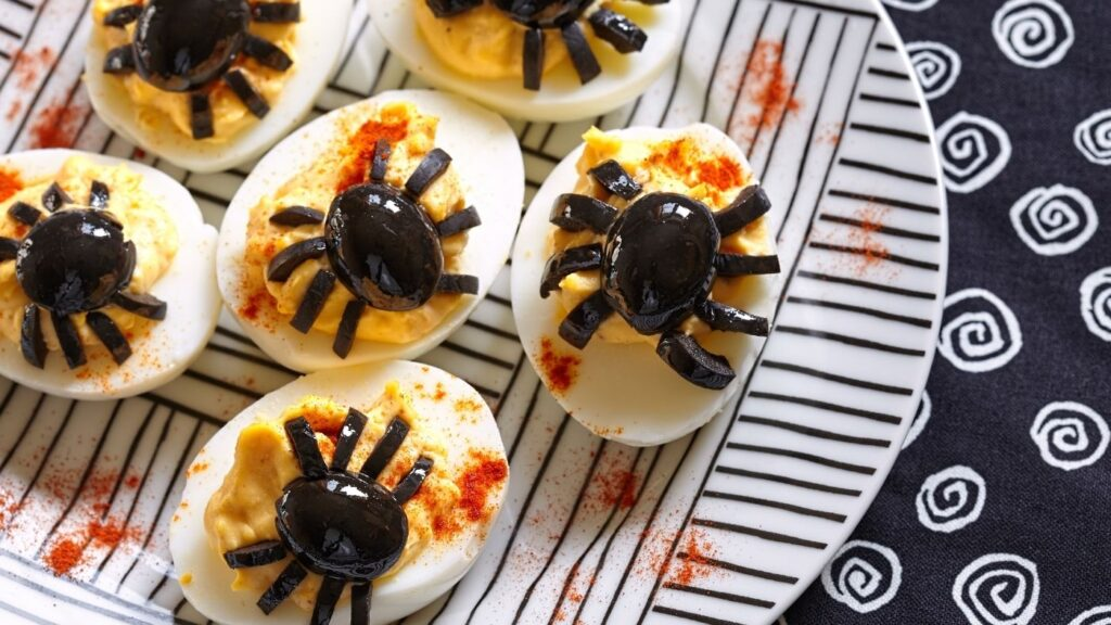 Halloween food - olive spiders on top of deviled eggs