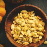 How to Roast Pumpkin Seeds - Roasted Pumpkin Seeds in a Wooden bowl next to a pumpkin