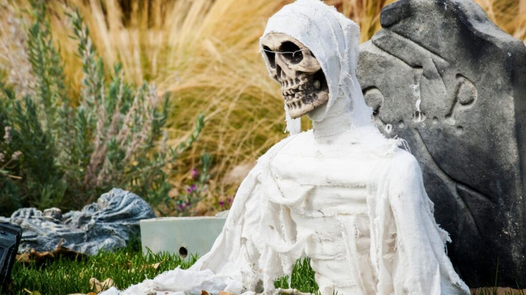Ideas for Halloween Decorating - gravestones with skeletons and gauze emerging from the ground.