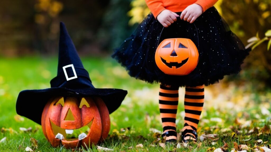 Ideas for Halloween Decor - Bottom half of a child's body dressed in a Halloween dress carrying a pumpkin bucket.  Next to her is a pumpkin with a hat.