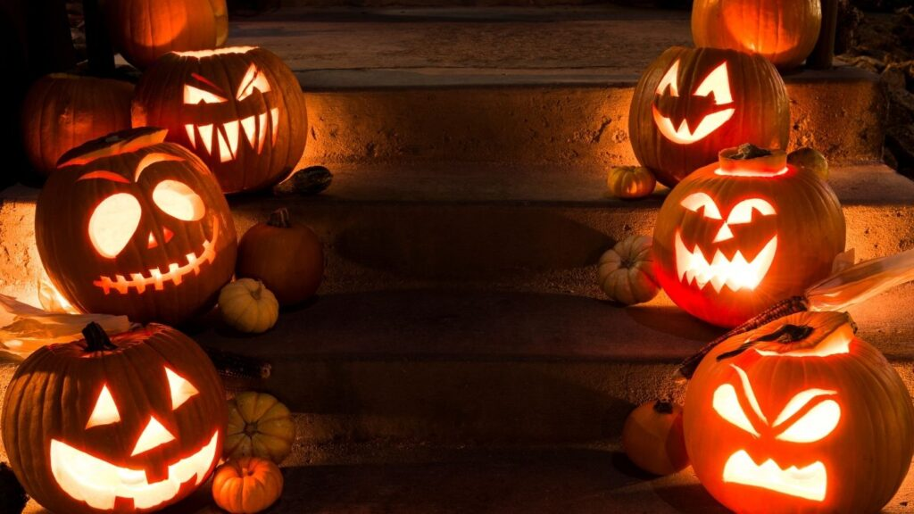 Six carved pumpkins lined up on the front porch steps, three on each side.
