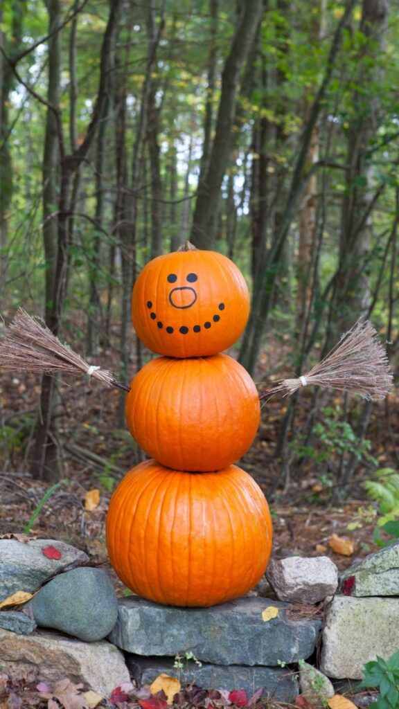 Snowman made of pumpkins and two twig brooms.