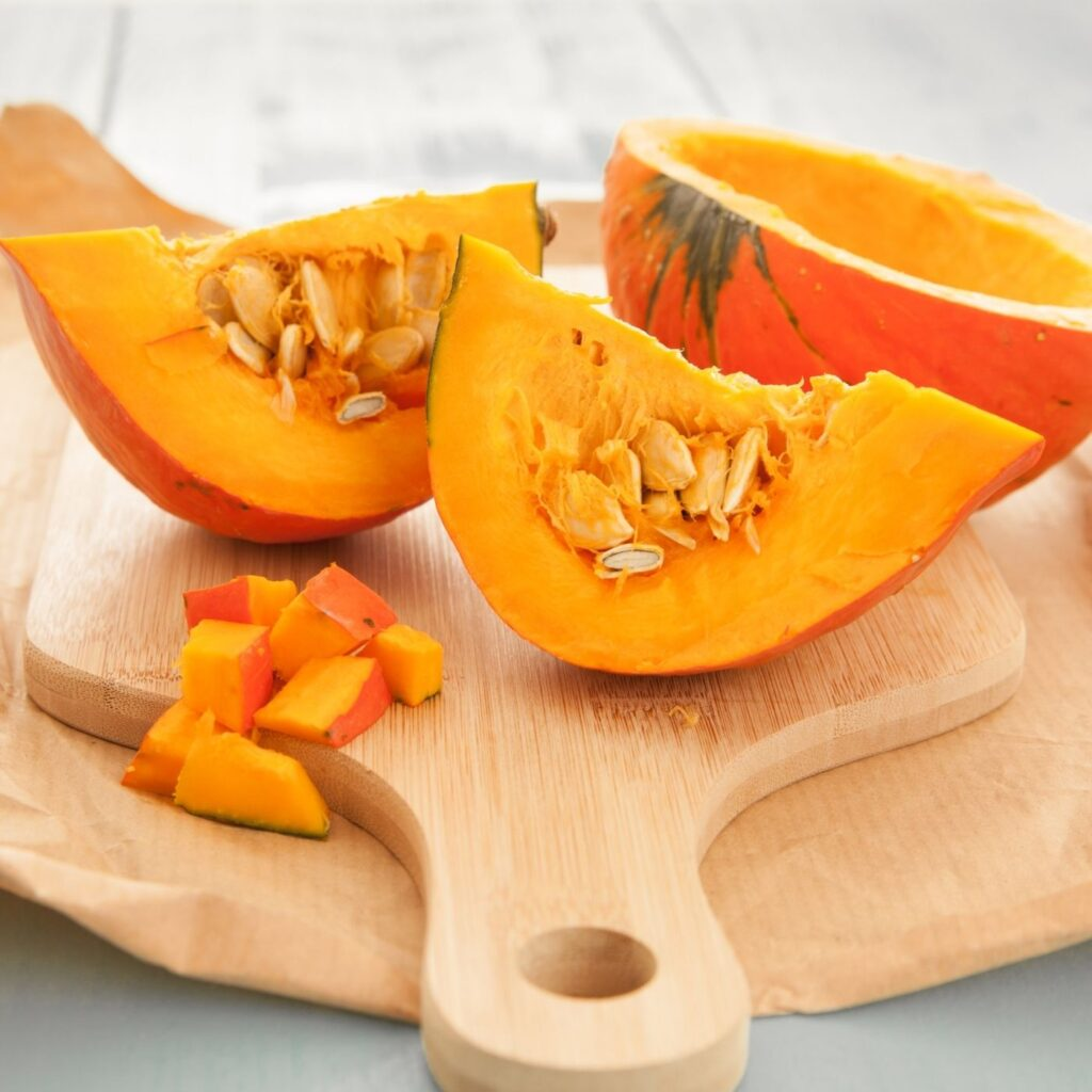 Raw Pumpkin cut up into slices with pumpkin seeds