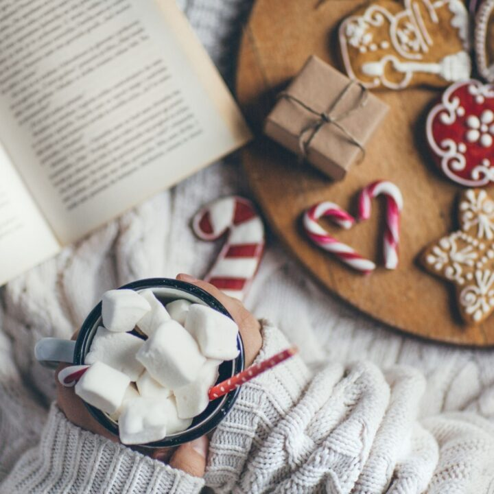 21 Hygge Christmas Ideas to Warm Your Soul - Wood tray with Christmas cookies, book, woman holding hot chocolate