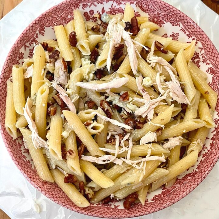 Balsamic Chicken Gorgonzola Pasta in a red and white bowl on a white plate