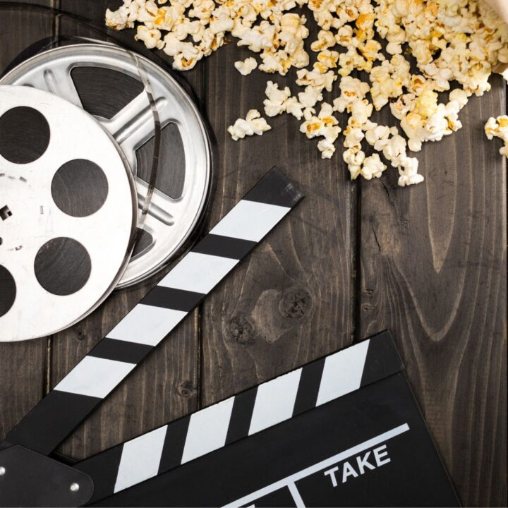 Best Hygge Movies to Watch Tonight - spilled popcorn and movie reels on a rustic surface