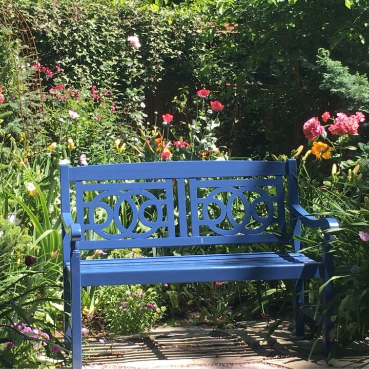 How to Make a Backyard Hygge Garden - Blue bench in front of flowers in a garden