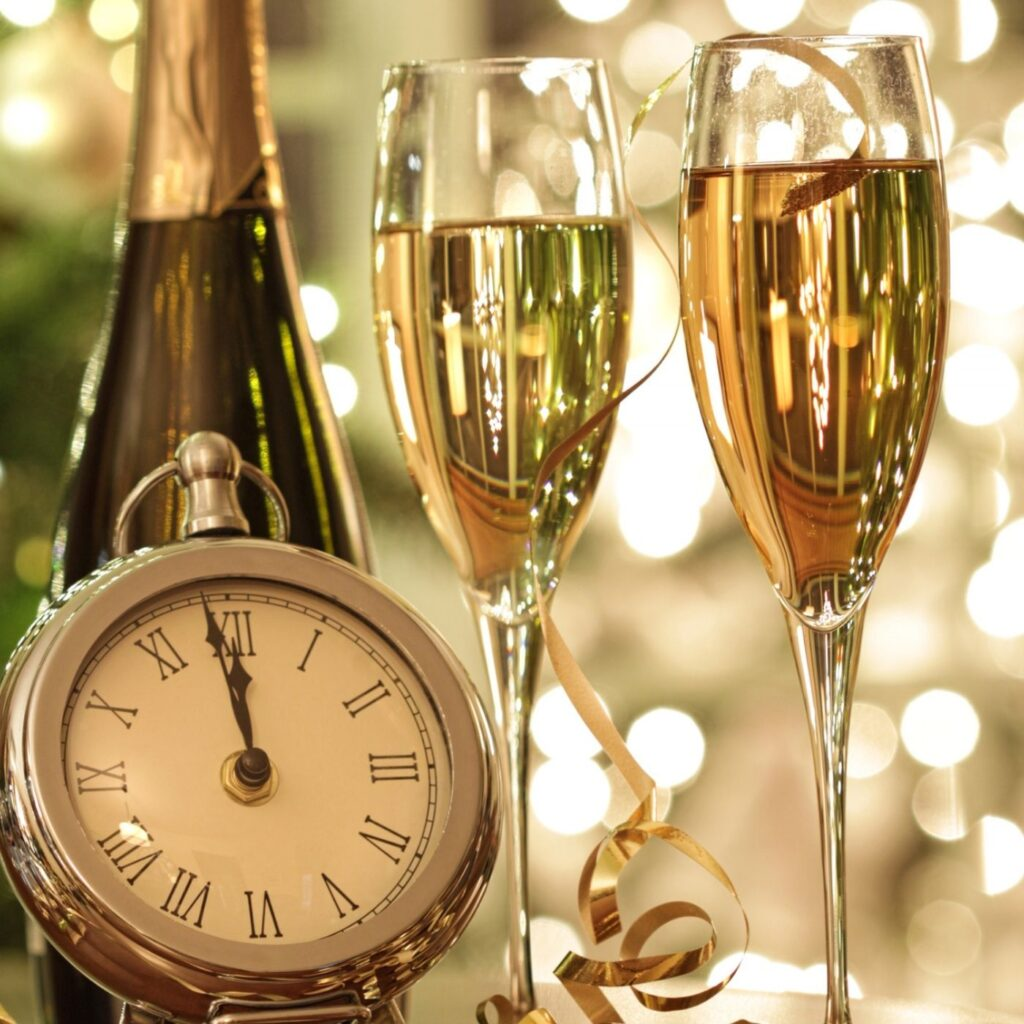 Hygge New Year Traditions - Bottle of champagne, two flutes of champagne, and clock.