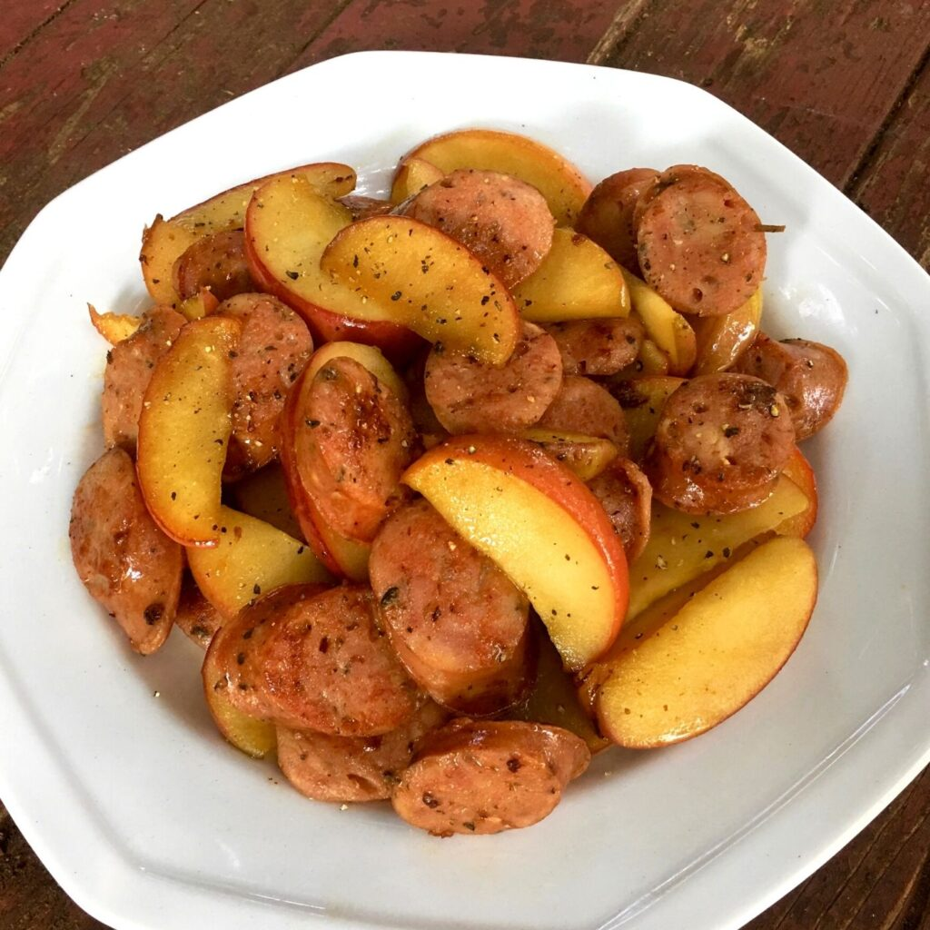 Skillet Chicken Sausages and Apples in a White bowl on a rustic surface